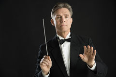 Confident Orchestra Conductor Directing With His Baton. Confident mature male orchestra conductor directing with his baton against black background Royalty Free Stock Photo