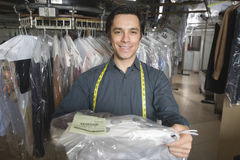 Confident Owner Giving Dry Cleaned Clothes In Laundry Stock Image