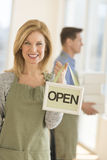 Confident Owner Holding Open Sign In Cafe Stock Photo