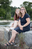 Confident Parent. Mother and teenage daughter sitting together outdoors with a safe, happy expression Stock Image