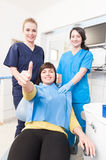 Confident patient with doctor and assistant showing thumb up Stock Images
