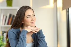 Confident pensive woman looking at side at home stock photo