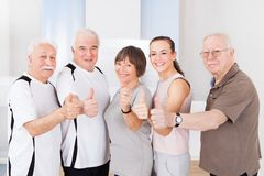 Confident people showing thumbs up at healthclub Royalty Free Stock Photography