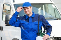 Confident Pest Control Worker Wearing Cap Against Truck. Portrait of confident pest control worker wearing cap against truck stock photo