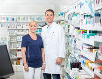 Confident Pharmacist And Assistant Standing In Stock Images