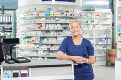 Confident Pharmacist Leaning At Cash Counter In Stock Photo
