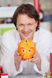 Confident pharmacist showing piggy bank Stock Photography