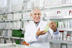 Confident Pharmacist Smiling While Holding Product In Pharmacy. Portrait of confident pharmacist smiling while holding product in pharmacy stock photo