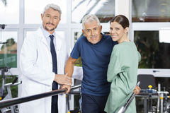 Confident Physiotherapists With Senior Patient In Fitness Studio Stock Photography