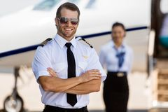 Confident Pilot Against Stewardess And Private Jet royalty free stock image