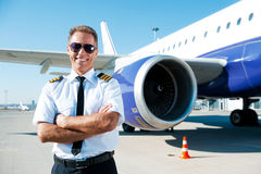 Confident pilot. Confident male pilot in uniform keeping arms crossed and smiling with airplane in the background stock photo