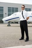Confident Pilot With Private Jet In Background. Full length of confident pilot with private jet in background Stock Photo