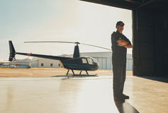Confident pilot standing in airplane hangar. Full length portrait of confident pilot standing with his arms crossed in airplane hangar with a helicopter in Royalty Free Stock Photo