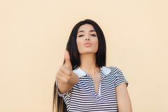 Confident pleased young woman with self assured expression, keeps thumb raised, shows approval gesture, has healthy skin, lips rou royalty free stock images