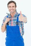 Confident plumber holding tool while gesturing thumbs up. Portrait of confident plumber holding tool while gesturing thumbs up over white background Royalty Free Stock Photo
