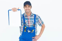 Confident plumber showing blank clipboard Stock Image