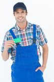 Confident plumber showing green card Stock Image