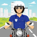 Confident policeman with sunglasses riding motorcycle through the city streets Stock Photo