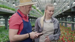 Confident positive Caucasian man teaching young beautiful woman in greenhouse. Professional experienced male biologist