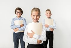 Confident positive children are expressing gladness. Successful smart team concept. Portrait of joyful optimistic kids are standing with documents and looking at royalty free stock images