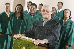 Confident Preacher Standing At Pulpit With Choir In Background. Portrait of confident senior preacher standing at pulpit with choir in background at church stock photography