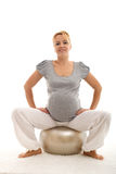 Confident pregnant woman sitting on exercise ball Stock Photo