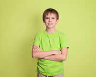 Confident preteen boy portrait with arms crossed isolated on green background.