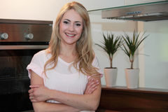Confident Pretty Blond Woman at Home. Close up Confident Pretty Blond Woman, in Casual Shirt, Posing at the Kitchen While Looking at the Camera Royalty Free Stock Photography