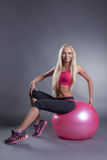 Confident pretty blonde posing with gymnastic ball Stock Photo