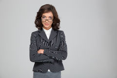 Confident pretty businesswoman in glasses standing with crossed arms. Confident pretty young curly businesswoman in glasses and gray jacket standing with crossed royalty free stock images