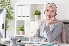 Confident pretty female muslim office operator