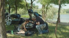 Stylish woman biker repairing motorcycle in park stock video footage