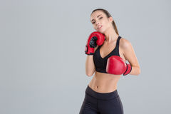 Confident pretty fitness girl posing in red boxing gloves Stock Photo