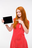 Confident pretty redhead girl pointing on blank screen digital tablet Stock Photos