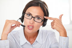 Confident pretty woman conversing on headset Stock Photo