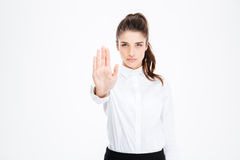 Confident pretty young businesswoman standing and showing stop gesture royalty free stock photography