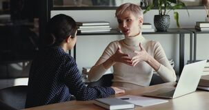 Confident professional female mentor training employee in office