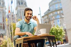 Confident professional guy employing special equipment. How can I help you. Savvy charismatic motivated man working distantly as a customer support Royalty Free Stock Photos