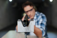 Confident professional marksman aiming at you. Being at gunpoint. Confident professional nice marksman holding a rifle and aiming at you while visiting shooting stock photography