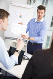 Confident Professional Showing Chart To Colleagues Royalty Free Stock Photography