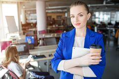 Confident and professional woman is standing in the office and holding a cup of coffee. Also she has a notebook in her. Hands. Woman is looking straight to the royalty free stock images