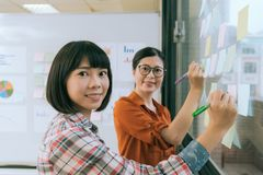 Confident professional women designer team. Face to camera when they meeting on glass wall and using color pen writing note in sticky memo paper stock photo