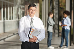 Confident Professor With Books Standing On College. Portrait of confident male professor with books standing on college campus stock photos