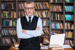 Confident professor. Confident grey hair senior man in formalwear keeping arms crossed and looking at camera while leaning at the table and with bookshelf in Stock Photo