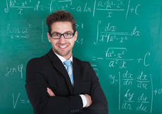 Confident Professor Standing Against Blackboard Stock Image
