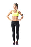 Confident proud athletic sporty female jogger with hands on waist looking down Royalty Free Stock Image