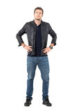 Confident proud casual man wearing jacket and jeans with hands on hips looking at camera Royalty Free Stock Photography