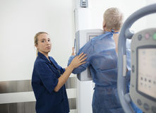Confident Radiologist Preparing Patient For Xray Royalty Free Stock Images