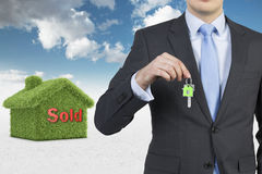 Confident real property agent is offering a key from a recently sold family house. Confident real property agent is offering a key from a recently sold family Royalty Free Stock Photo
