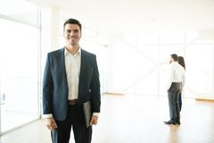 Confident Realtor Smiling With Clients In Background At New Home. Confident mid adult male realtor smiling with clients in background at new home royalty free stock image